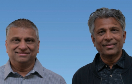 The image depicts the two founders of the company, Raj and Akhil Shah. They are standing in front of a blue background and smiling.